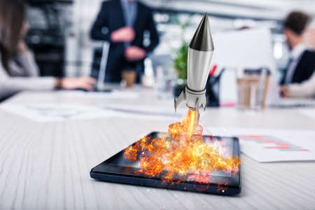 Rocket ready to starts from a tablet. concept of company startup Stock Photo