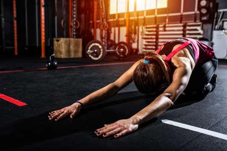 Entschlossenes athletisches Mädchen tut Ausdehnungsübungen an der Turnhalle Standard-Bild - 94745470
