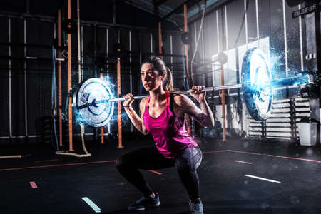 Athletic girl works out at the gym with a barbell with blue energy effects