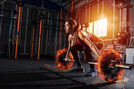 La ragazza atletica risolve in palestra con un bilanciere ardente Archivio Fotografico - 94766416