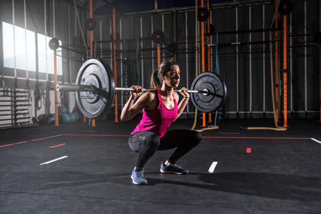 Athletic girl works out at the gym with a barbell Foto de archivo