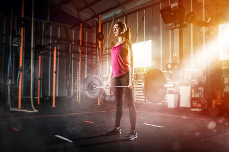 Athletic girl works out at the gym with a barbell Standard-Bild