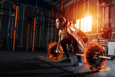 Athletic girl works out at the gym with a fiery barbell