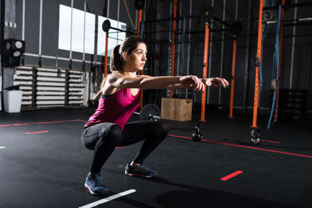Athletic girl does squat exercises at the gym Standard-Bild