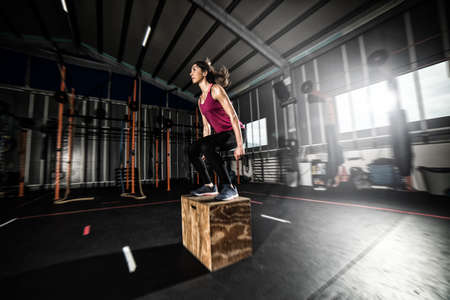 Athletic girl does box jump exercises at the gym Standard-Bild