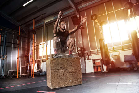 Athletic man does box jump exercises at the gym