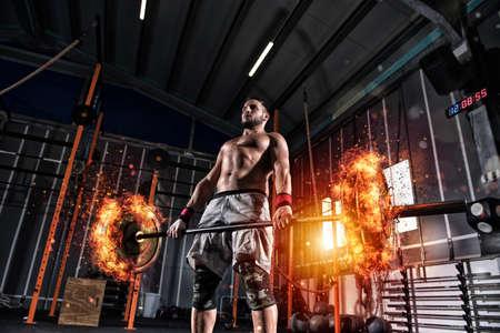 Uomo atletico si allena in palestra con un bilanciere infuocato Archivio Fotografico