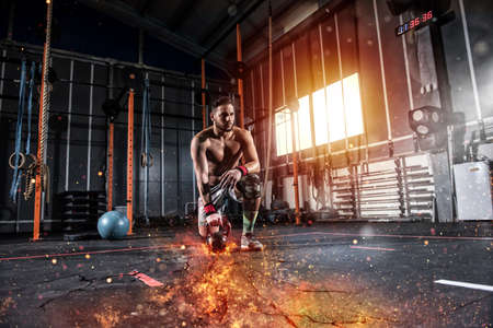 Athletic boy works out at the gym with a fiery kettlebell Standard-Bild