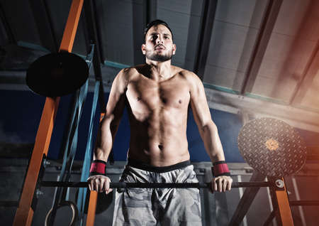 Athletic man works out at the gym with the bar