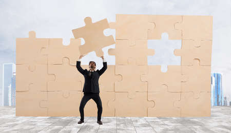 Businessman with a piece of puzzle. Build the business concept