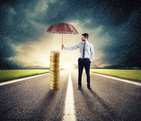 Businessman protects his money savings with umbrella. concept of insurance and money protection Stock Photo