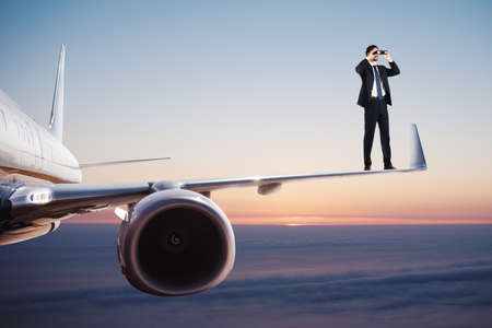 Businessman with binoculars over an aircraft searches for new business opportunities