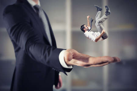 Businessman is saved from a big hand. Concept of business support and assistance