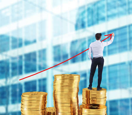Businessman draws growing arrow of company statistics over a pile of money Stock Photo