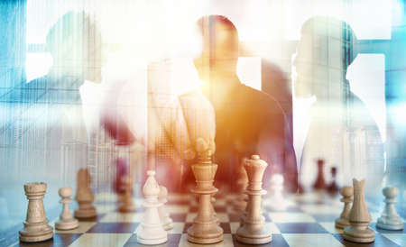 Business tactic with chess game and businessmen that work together in office. Concept of teamwork, partnership and strategy. double exposure 스톡 콘텐츠