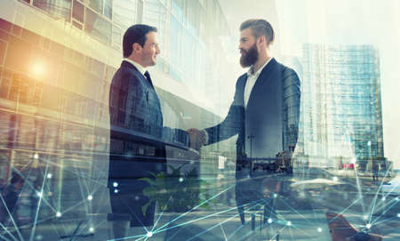 Handshaking business person in office. concept of teamwork and partnership. double exposure Banco de Imagens