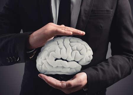 L'homme protège un cerveau avec ses mains. Rendu 3D Banque d'images