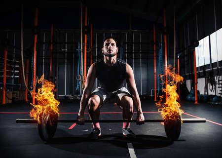Athletischer Mann arbeitet in der Turnhalle mit einer feurigen Langhantel Standard-Bild - 99152983