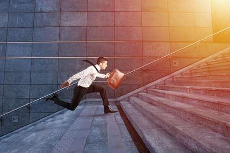 Businessman runs fast over a modern staircase Foto de archivo