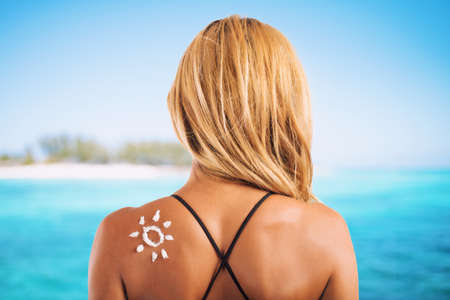 Girl in swimsuit with a sun made with sunscreen
