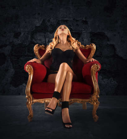 Sensual woman on a red velvet armchair Stok Fotoğraf