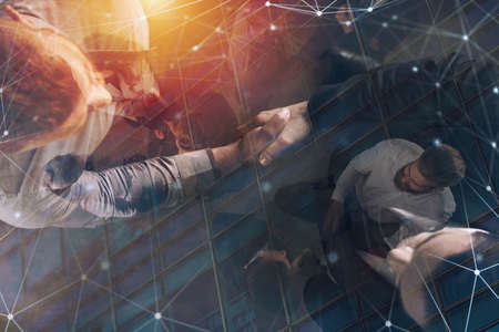 Handshaking business person in office with network effect. concept of teamwork and partnership. double exposure Archivio Fotografico