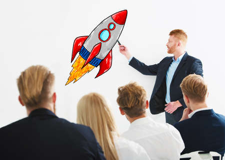 Businessman drawing a rocket during a training meeting. Concept of business improvement and enterprise startup