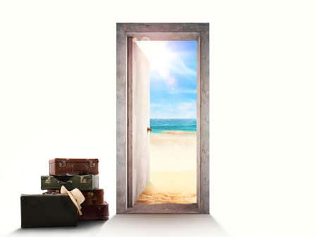 Door on white background leading to the beach with luggage on the floor. Banco de Imagens