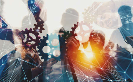 Business team connect pieces of gears. Teamwork, partnership and integration concept with network effect. double exposure 免版税图像