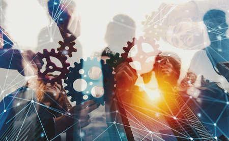 L'équipe commerciale connecte des pièces d'engrenages. Concept de travail d'équipe, de partenariat et d'intégration avec effet de réseau. double exposition Banque d'images