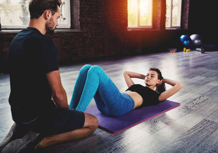 Personal trainer helps a girl with the gym exercises Stock Photo