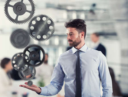 Businessman holds a gear system. Concept of business mechanism Stock Photo