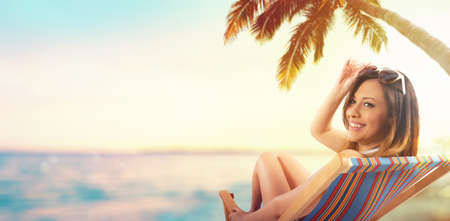 Beautiful girl sitting on a deck chair at the beach at sunset