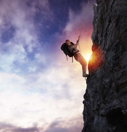 Man climbs a high danger mountain with a rope during sunset Stok Fotoğraf