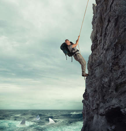 Explorer climbs a mountain with the risk to fall on the sea with sharks Stock Photo