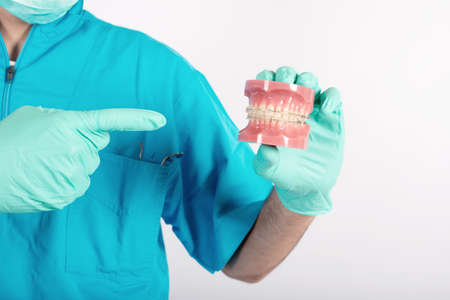 Dentist shows how to apply a brace