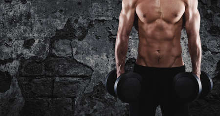 Athletic man training biceps at the gym Standard-Bild - 102368655