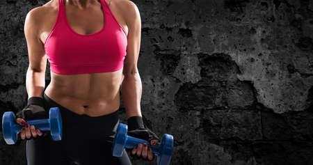 Athletic woman training biceps on grunge background