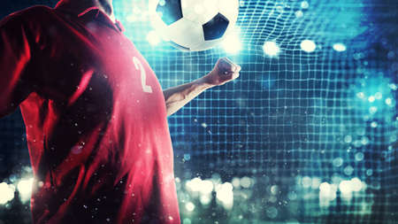 Striker player controls the ball near the football goal Фото со стока