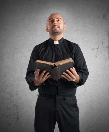 Priest praying to God while holding a Bible Banque d'images