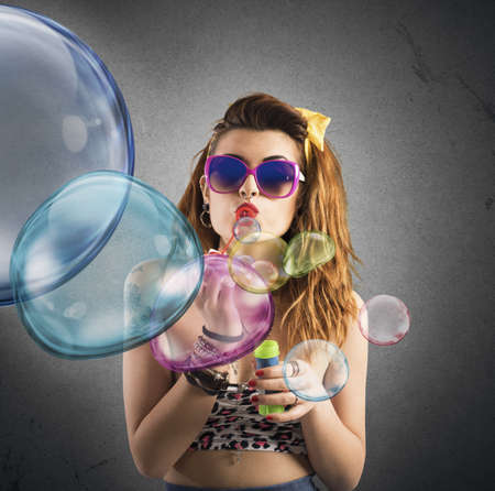 happy woman blowing colored bubbles
