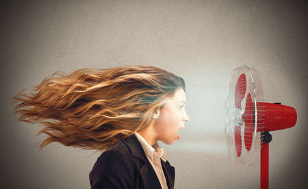 woman having a hot air from standing fans