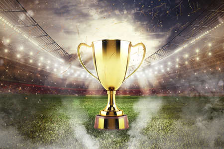 Golden winners cup in the middle of a stadium with audience Stock Photo