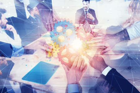 Business team connect pieces of gears. Teamwork, partnership and integration concept with network effect. double exposure Stock Photo
