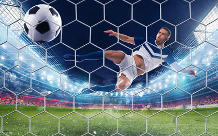 Soccer striker hits the ball with an jumping kick Stock Photo