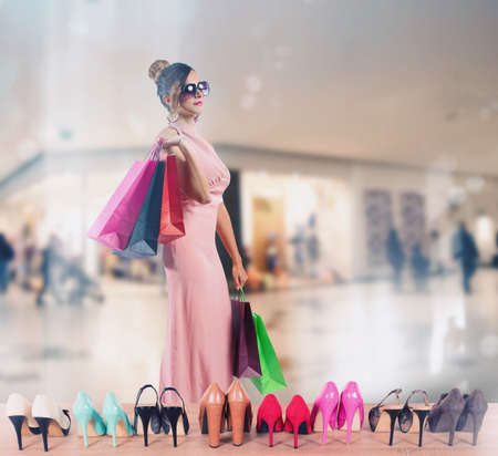 Girl full of bags does shopping in a store Stok Fotoğraf