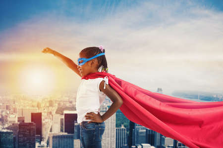 Child acts like a superhero to save the world Stock Photo