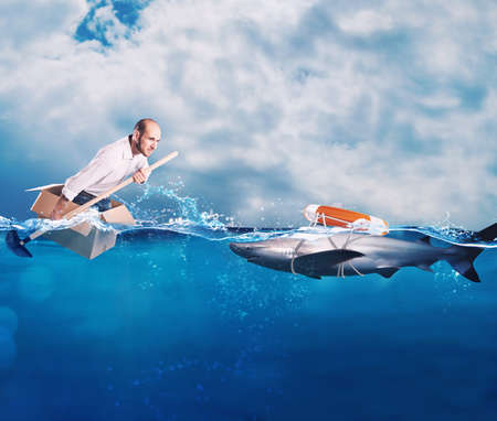 Businessman on a cardbox in the ocean looks for an help. Help with deception concept Stockfoto