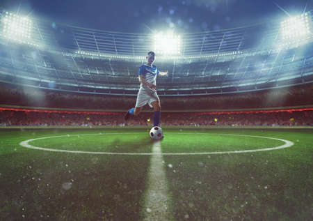 Soccer player hits the ball from the midfield at the stadium Фото со стока