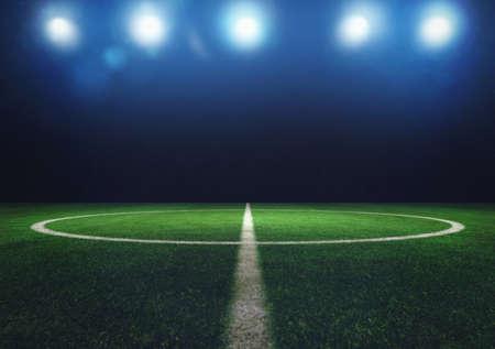 Centrocampo di campo da calcio in erba di notte con fari